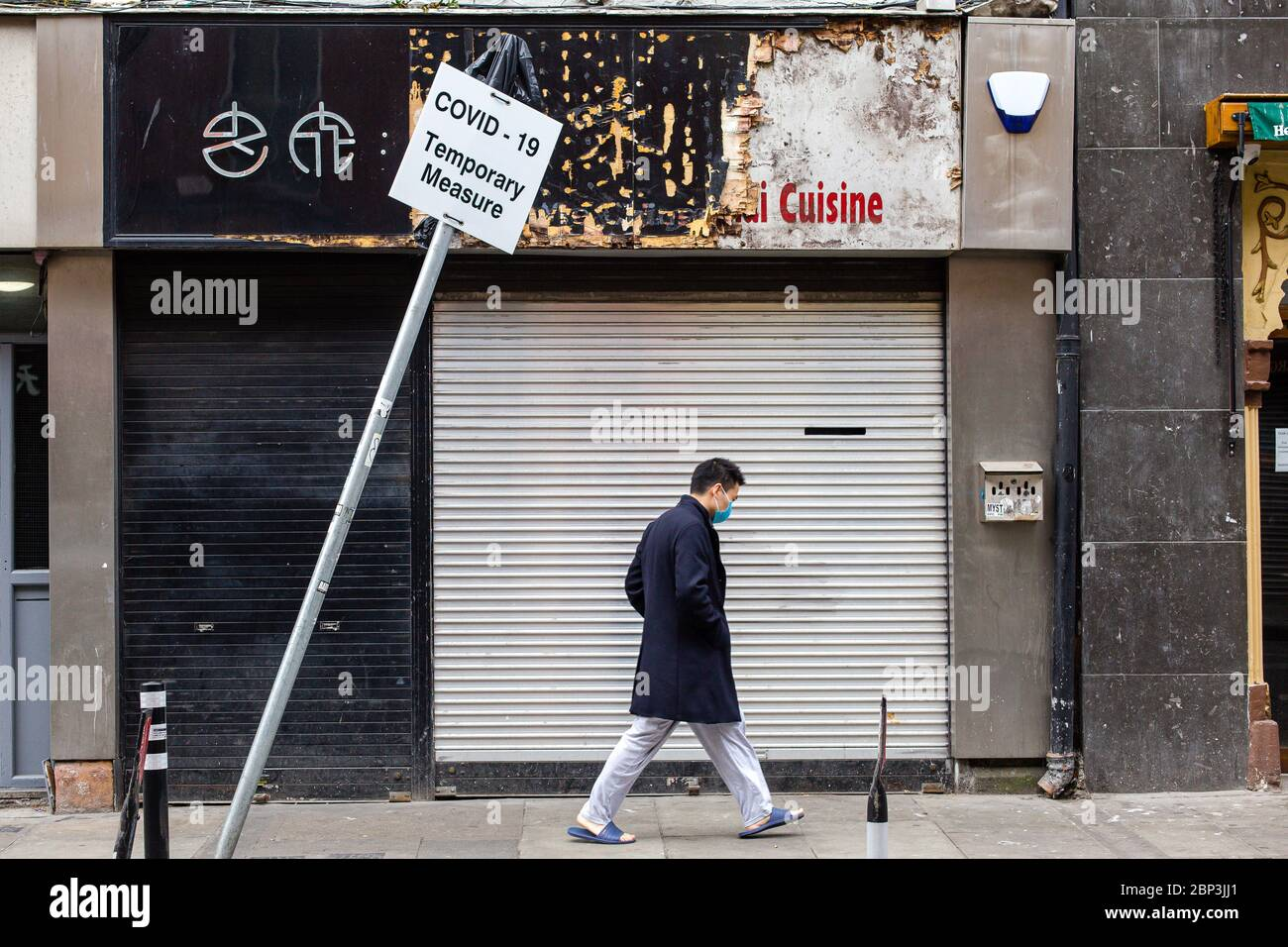 Asian Man wearing protective face mask passes by closed down shop and leaning sign - Covid-19 Temporary Measure. Coronavirus economic impact Ireland. Stock Photo