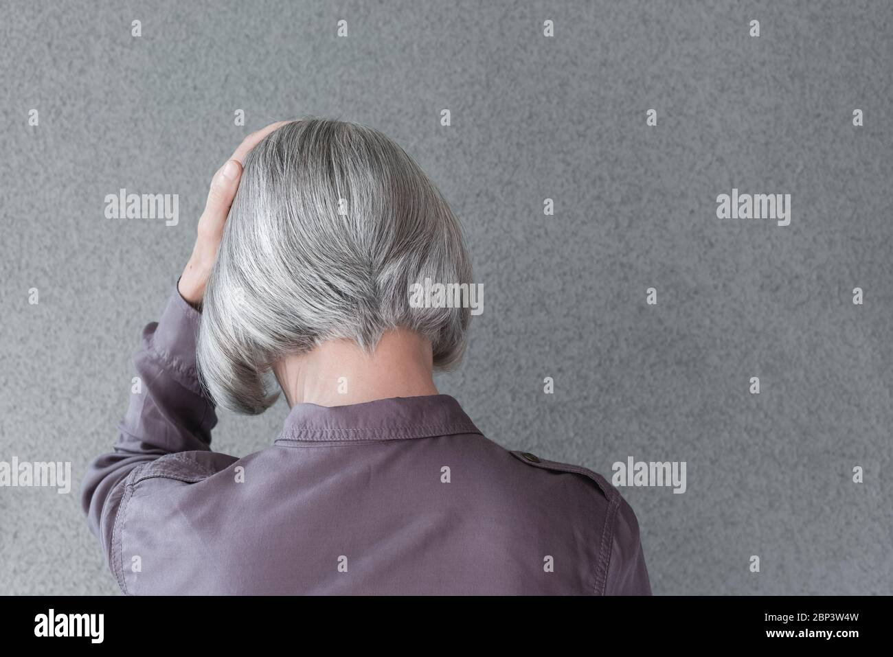 Upset gray-haired woman, holding her head with her hand, on gray background with copy space. Stock Photo