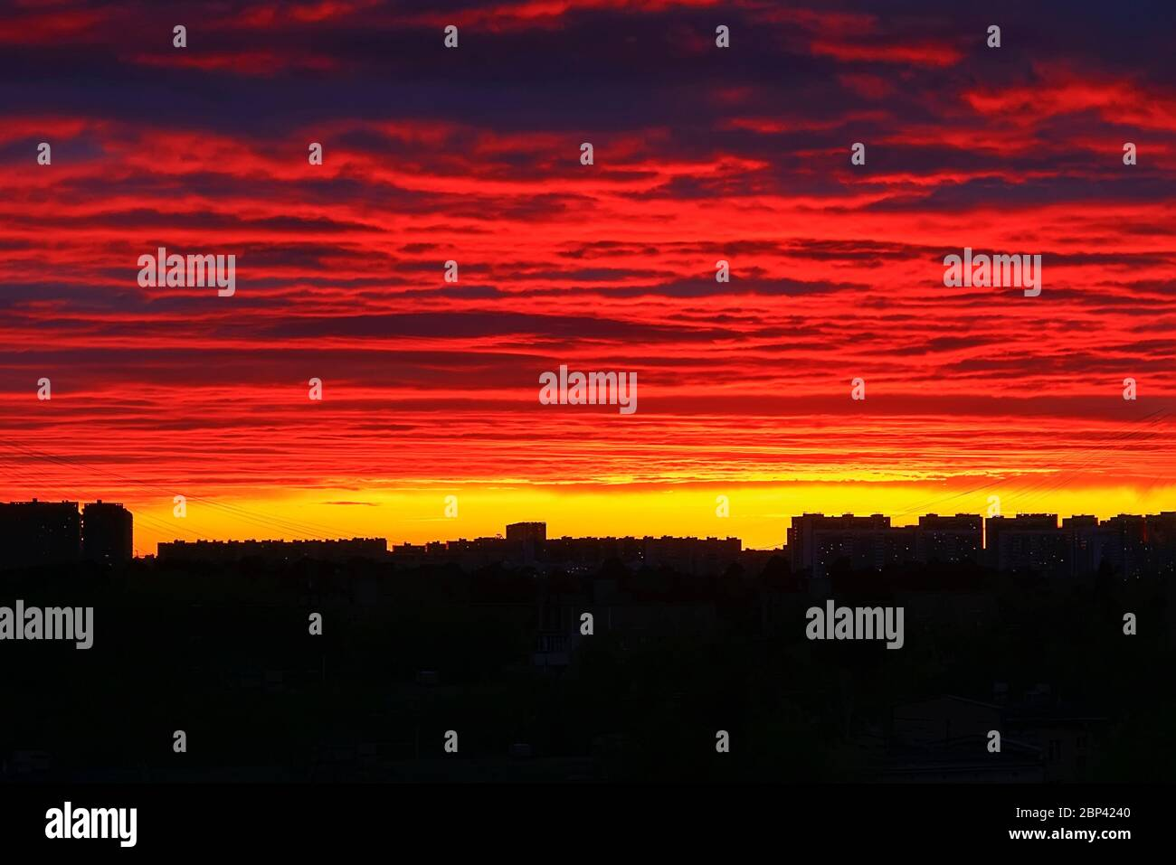 Bright fiery sunset over the dark silhouettes of houses, sky in the clouds, multi-colored paints . Stock Photo