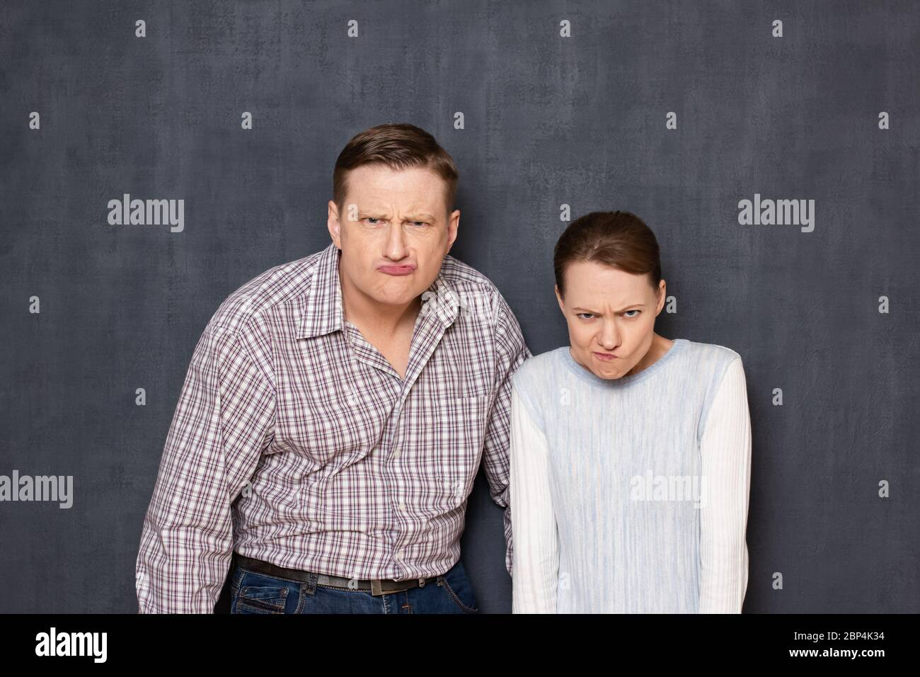 Studio waist-up portrait of funny caucasian young adult couple grimacing and making stupid angry faces, looking with dissatisfied expression from unde Stock Photo
