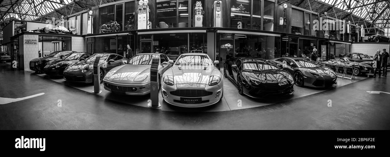 BERLIN - MAY 11, 2019: Panoramic view of the garage of Classic Remise Berlin, and repair and service offices - venue of 32th Berlin-Brandenburg Oldtimer Day. Various modern sports cars stand in a row. Black and white. Stock Photo