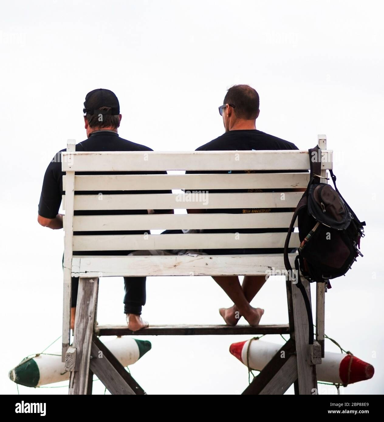 Rear view of two male lifeguards on duty sitting on a white guard towers with rescue flotation devices. Stock Photo