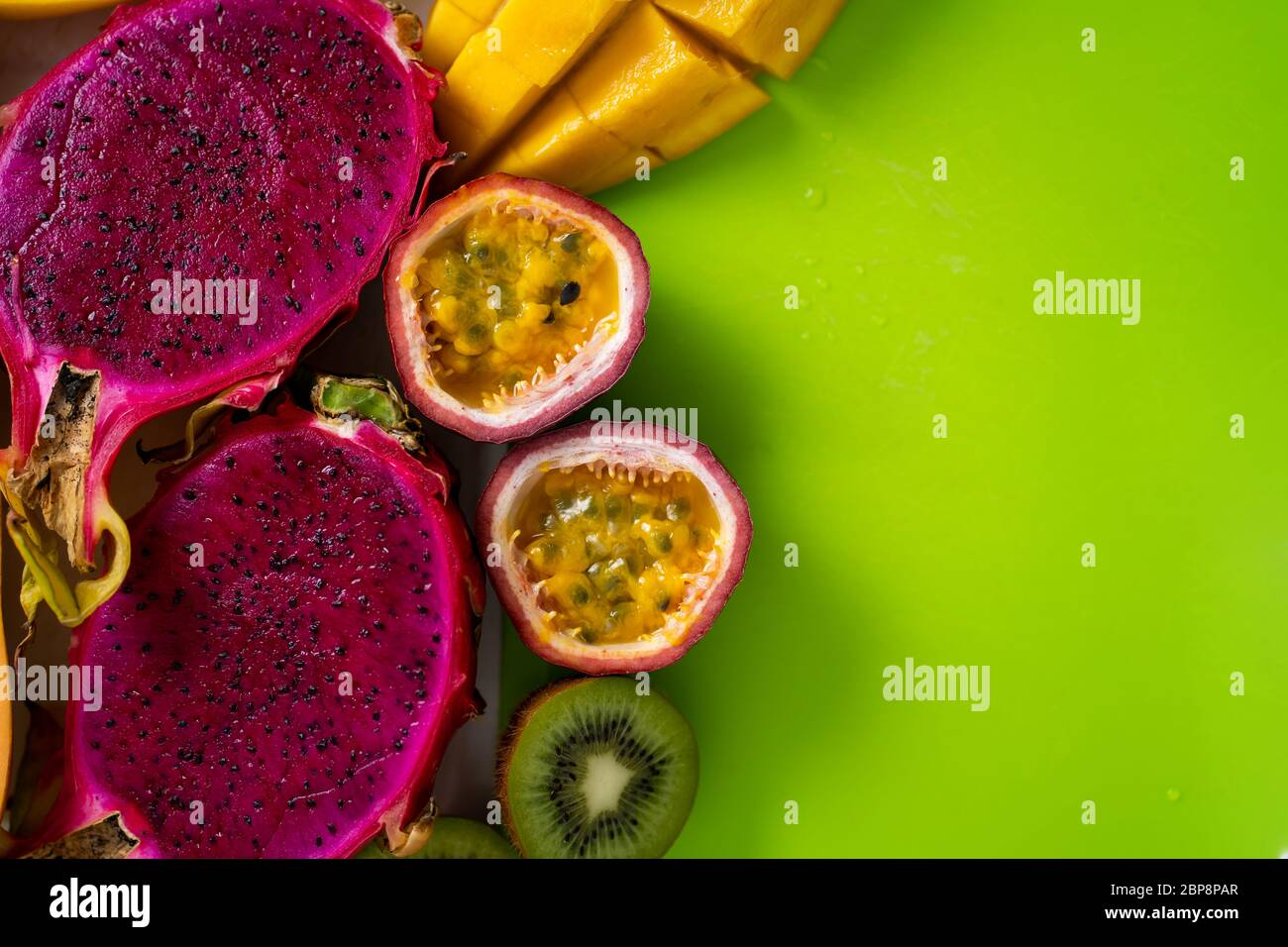 Closeup of sliced tropical exotic fruits on on green cutting board. Top view. Copy space for your text. Fresh mango, dragon fruit, kiwi, maracuja, pap Stock Photo