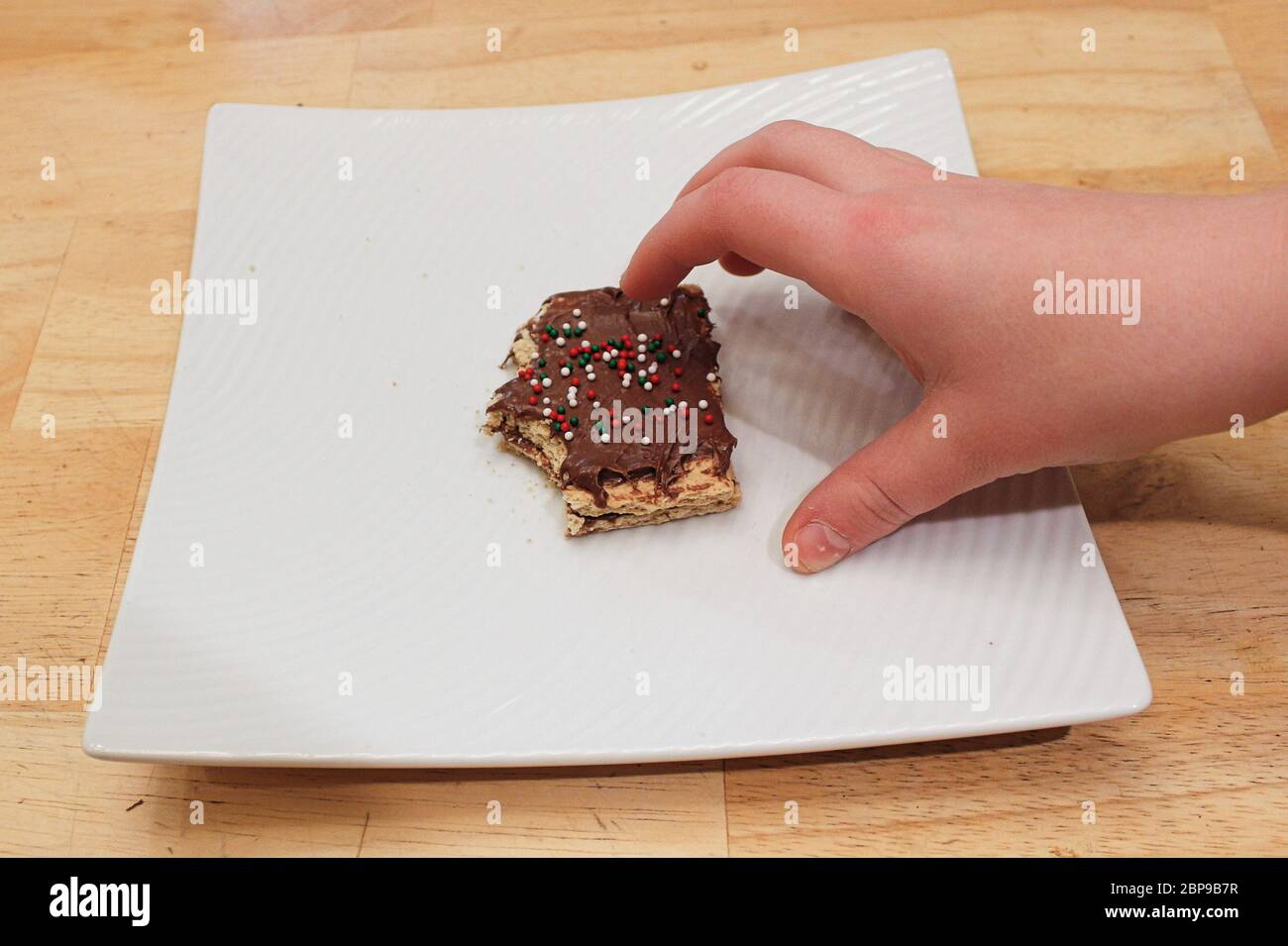 A childs hand grabing a treat off a white plate. Stock Photo