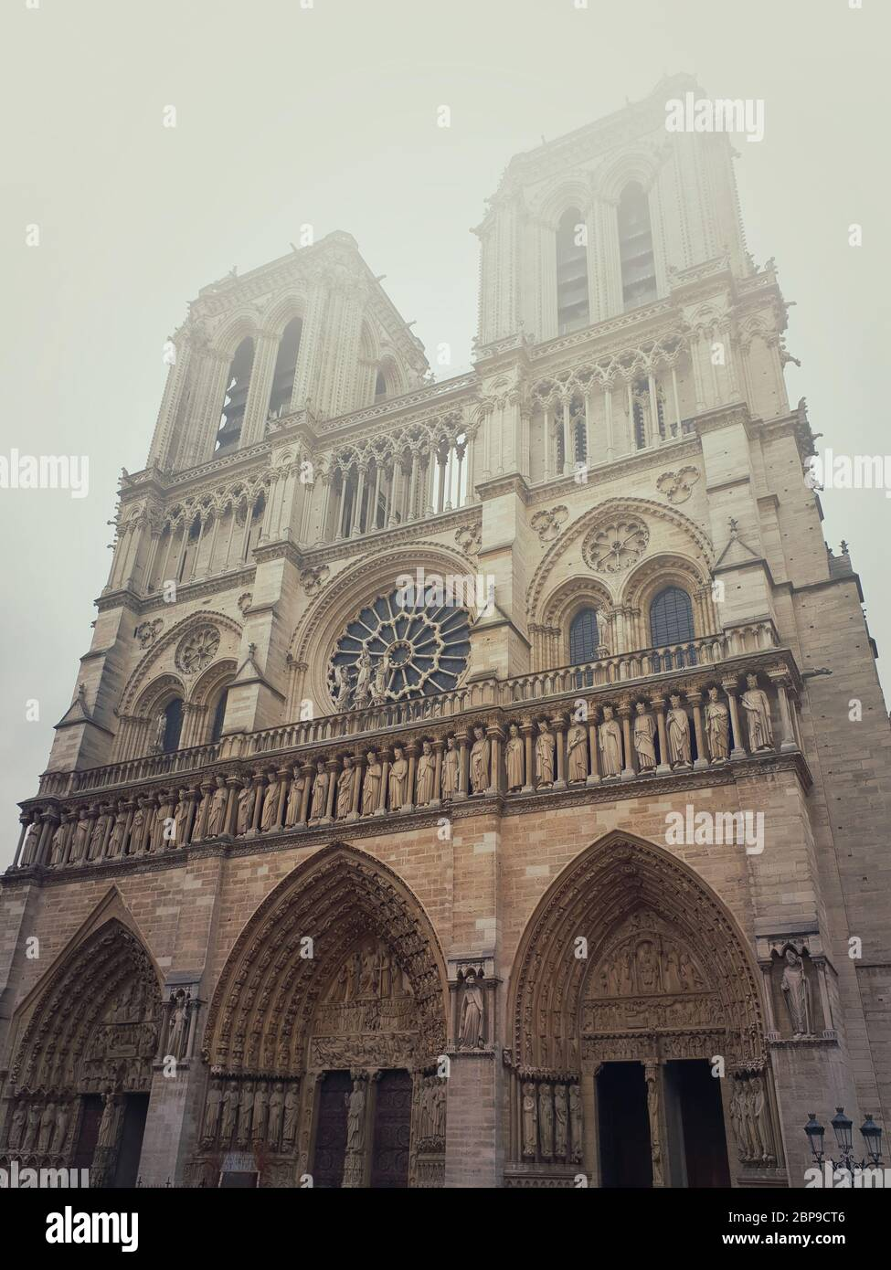 Notre Dame de Paris cathedral facade in a foggy morning. Gorgeous gothic architecture. Stock Photo