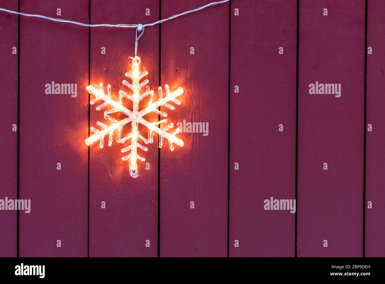 Electric star hanging outside wooden home during Christmas in winter Stock Photo
