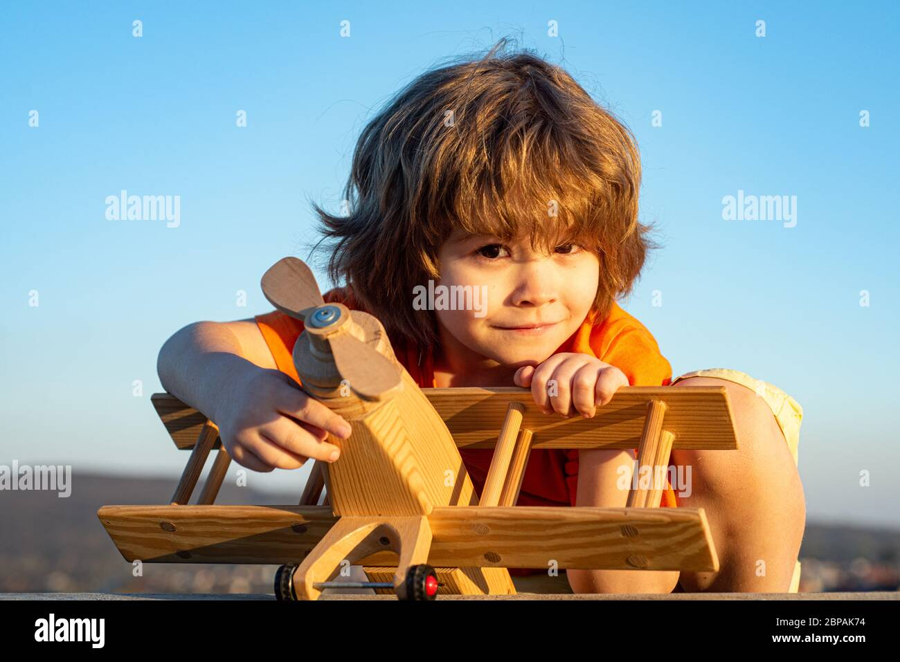 Happy child dreams of traveling and playing with toy airplane. Little pilot aviator in outdoor against blue summer sky background. Child dreams Stock Photo