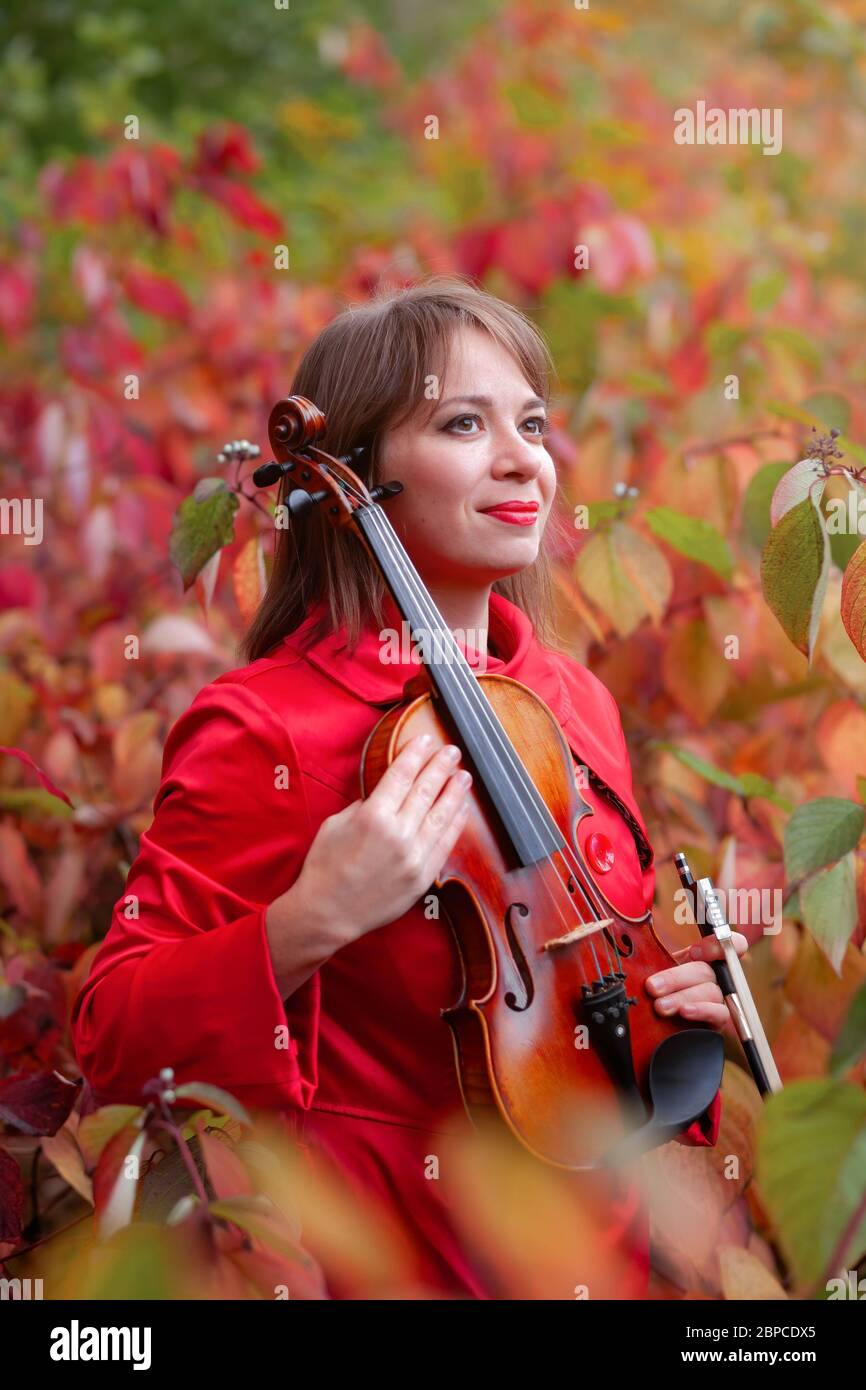 young beautiful woman in red coat holding violin in hands smiling and hiding among fall colored red and green leaves in autumn forest or park Stock Photo