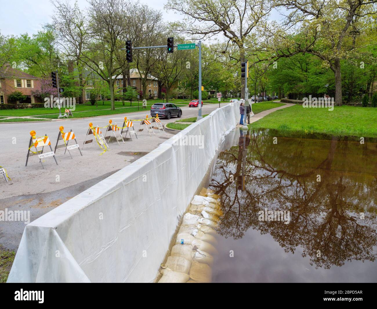 River Forest, Illinois, USA. 18th May 2020.  A temporary flood barrier constructed across Chicago Avenue holds Des Plaines River floodwater away from this western suburb of Chicago. Stock Photo