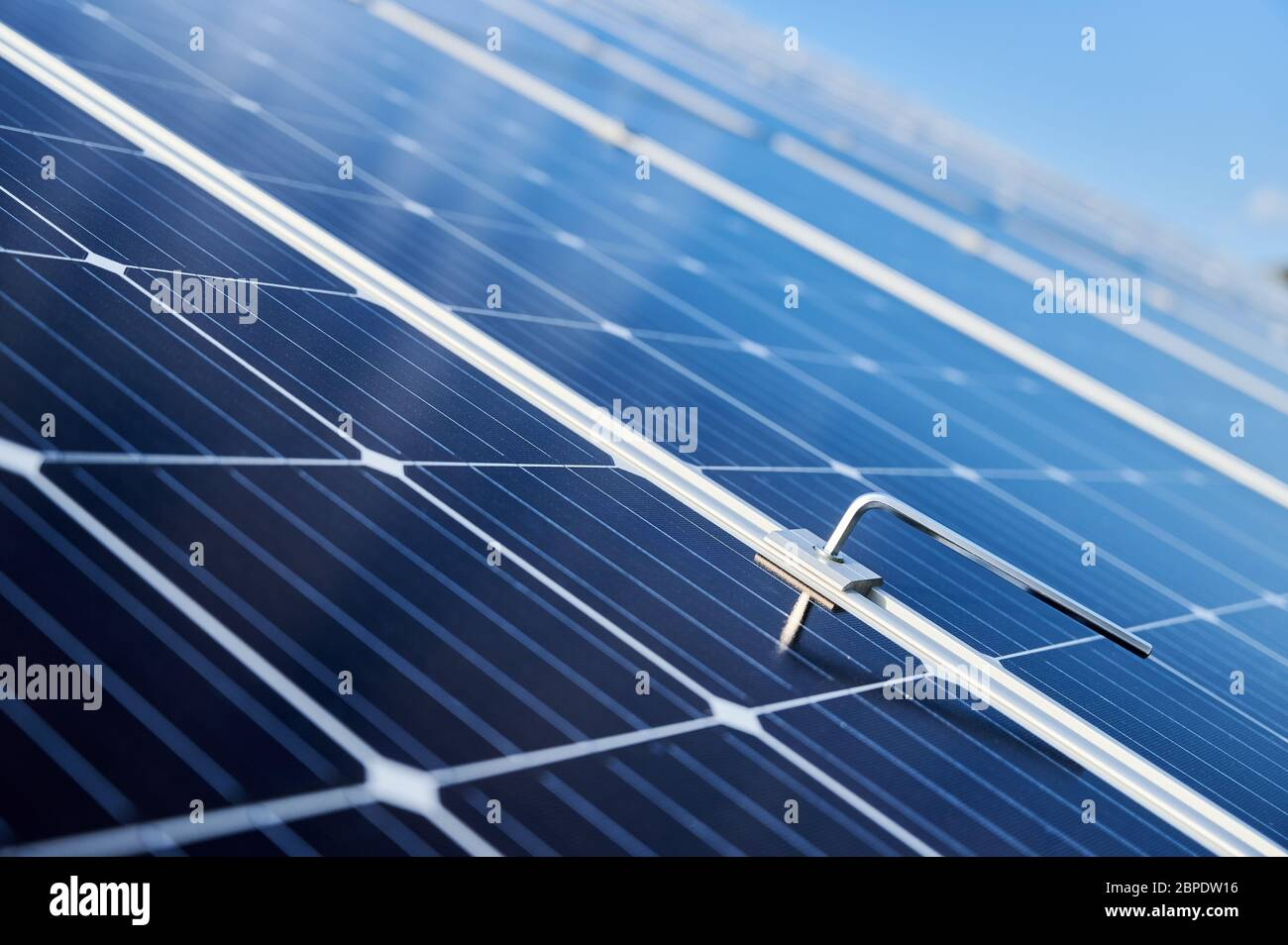 Close-up snapshot of a new blue shiny solar module and a hex key stuck in between. Green energy concept. Modern technologies, ecological solution, power sustainable resources concept Stock Photo