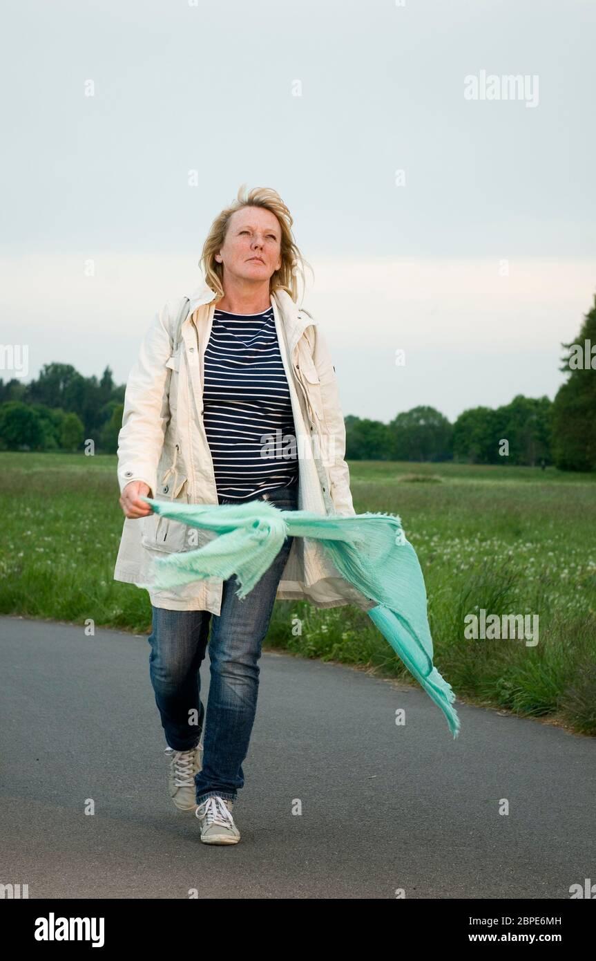 Ganzkörper-Porträt einer blonden reifen Frau in heller Jacke mit mintgrünem Schal sich auf einem asphlatierten Fußweg fröhlich um sich selbst drehend Stock Photo