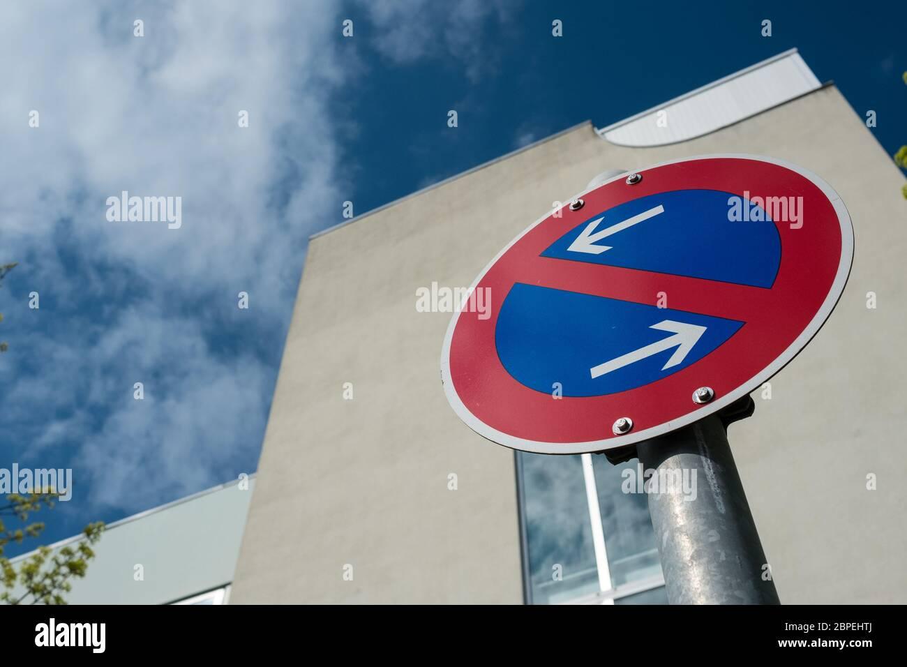 Schild eingeschränktes Halteverbot vor einem Gebäude mit Wolken Stock Photo