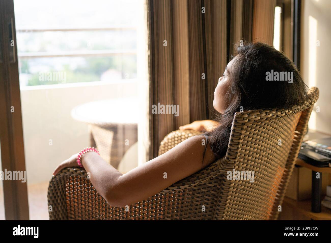 Concept image of the issues surrounding mental health.A woman sitting in a chair stares out of an open window during a quarantine period in the COVID-19 Pandemic 2020 Stock Photo