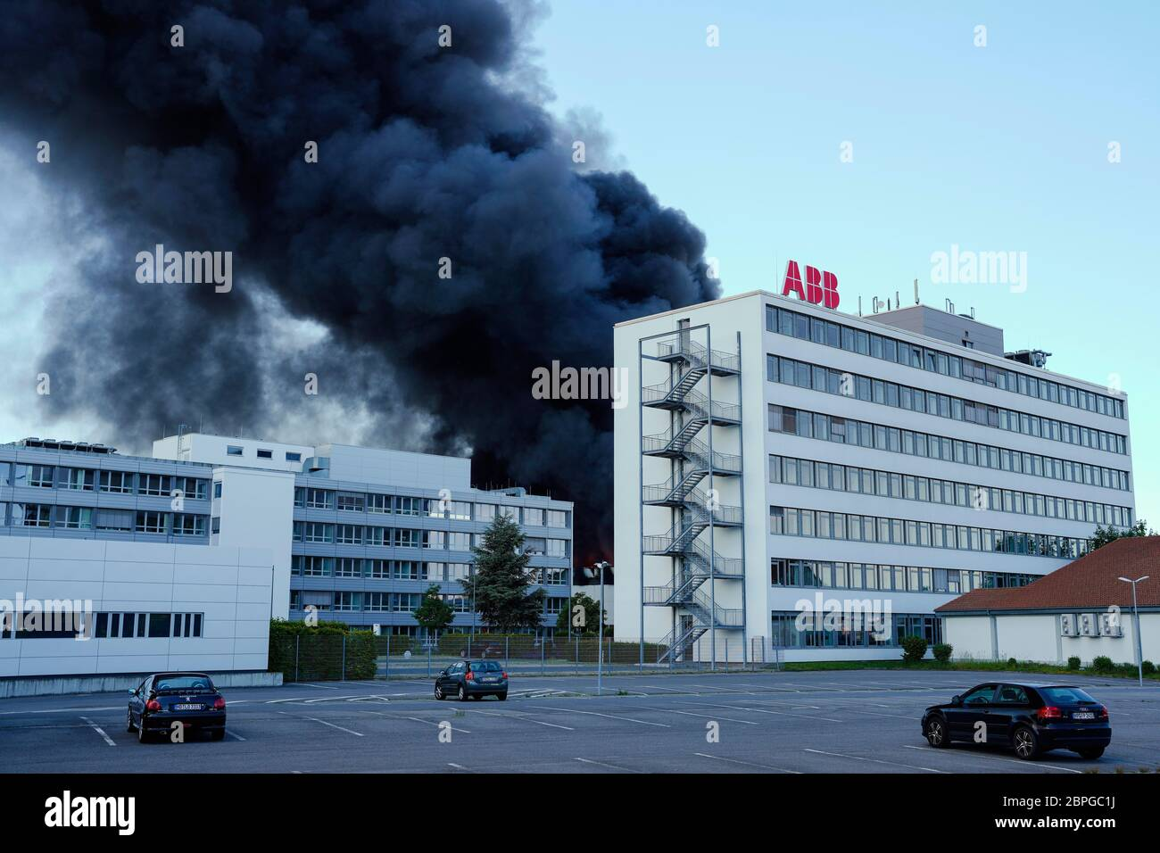Ladenburg, Germany. 19th May, 2020. Clouds of smoke rise from a plastics factory behind a building belonging to the ABB company. Due to a major fire in a factory building in Ladenburg (Rhine-Neckar district) a large cloud of smoke formed over the region. Credit: Uwe Anspach/dpa/Alamy Live News Stock Photo