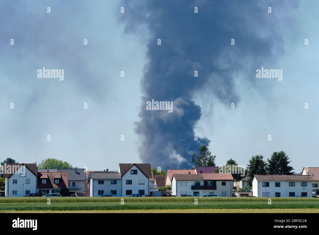 Ladenburg, Germany. 19th May, 2020. Clouds of smoke from a fire in a plastics factory rise into the sky behind houses. Because of the large fire in a factory building in Ladenburg (Rhine-Neckar district) a large cloud of smoke formed over the region. Credit: Uwe Anspach/dpa/Alamy Live News Stock Photo