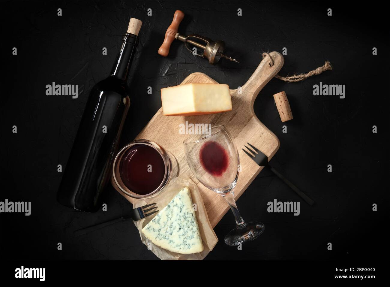Wine and cheese tasting, shot from above on a black background, with a vintage corkscrew and a bottle Stock Photo