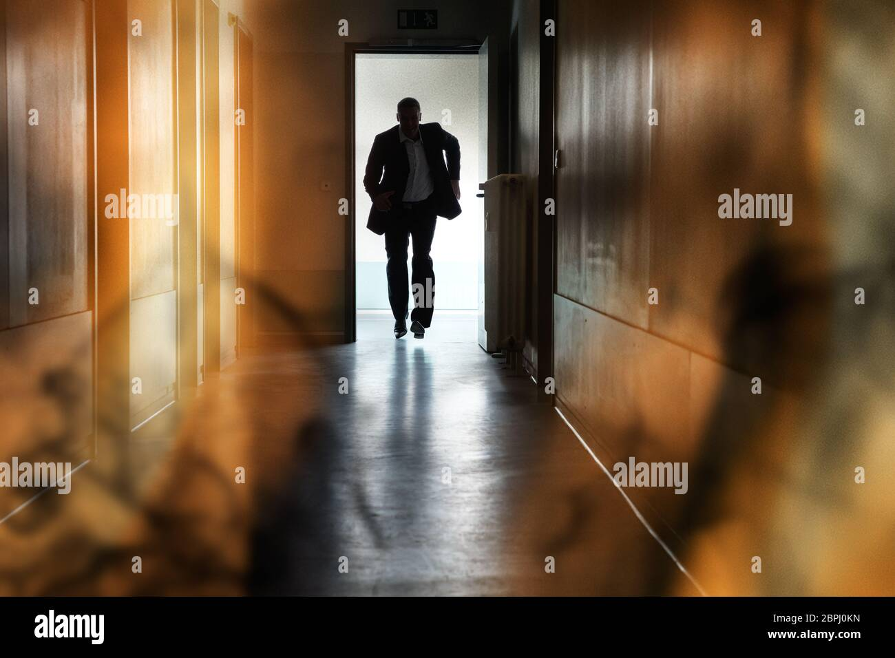 Silhouette Of Person Running Out Of Fire Escape On Corridor Of Building Stock Photo