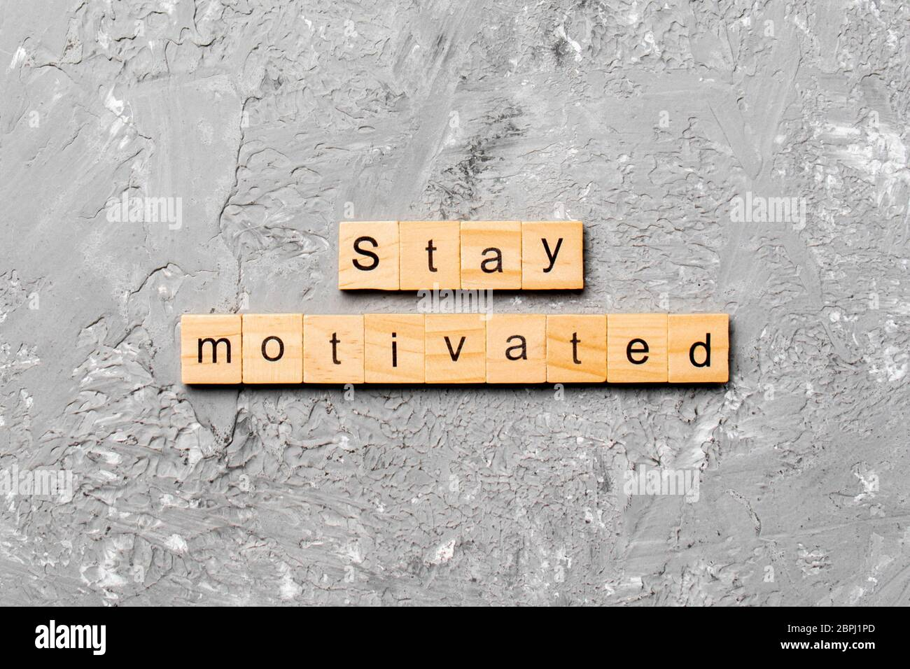 Stay motivated word written on wood block. Stay motivated text on cement table for your desing, concept. Stock Photo