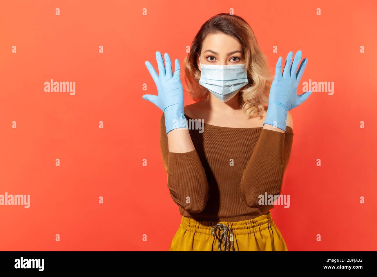 Portrait of woman wearing surgical face mask and gloves to prevent viral disease, coronavirus pandemic threat, 2019-ncov protection recommendations. i Stock Photo