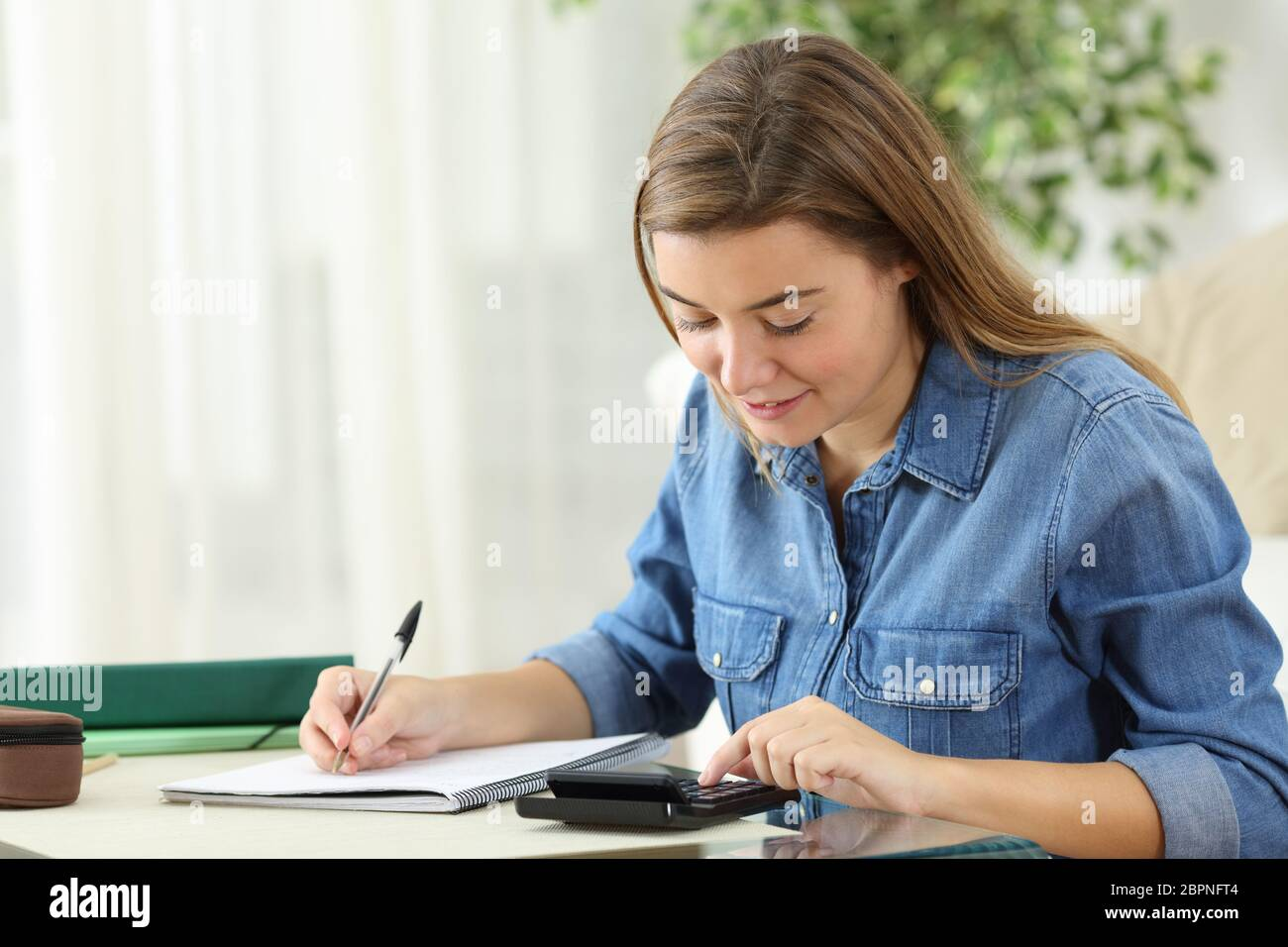 Student studying calculating with a calculator and handwriting notes siting on the floor in the living room at home Stock Photo