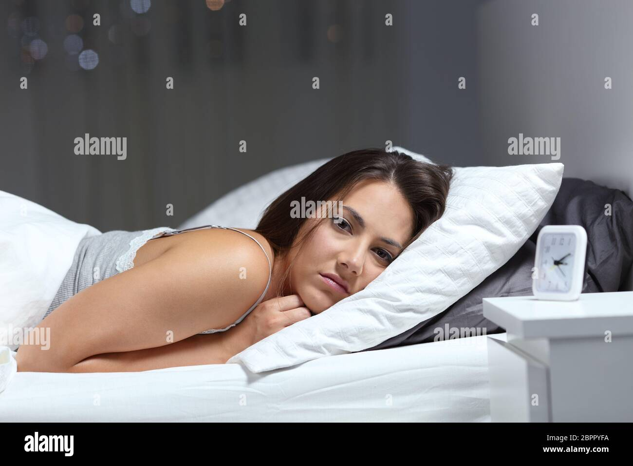Restless girl suffering insomnia looking at you in the bed in the night Stock Photo