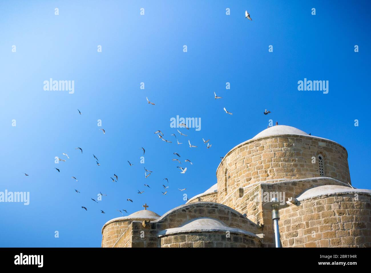 Flock of pigeons flying above the Church of the Apostles Barnabas and Hilarion (Agii Varnavas and Ilarionas) in Peristerona, Cyprus Stock Photo