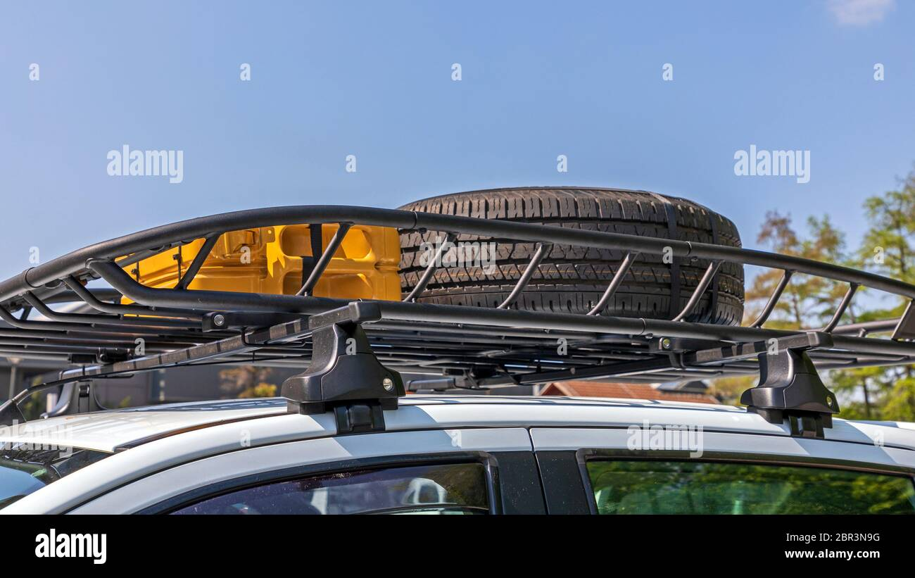 Spare Tyre and Jerry Can at Vehicle Roof Rack Stock Photo
