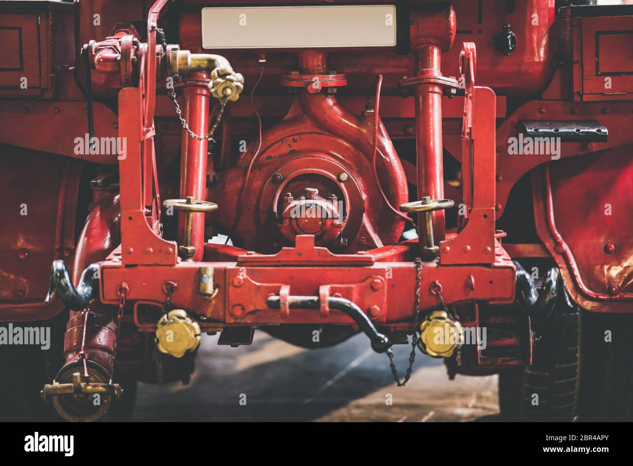 Back of a classic retro red fire truck with metal pipes Stock Photo