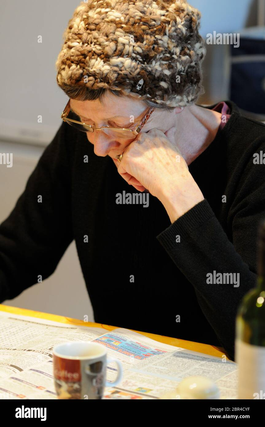 Middle-aged woman relaxing in a kitchen by reading a newspaper Stock Photo