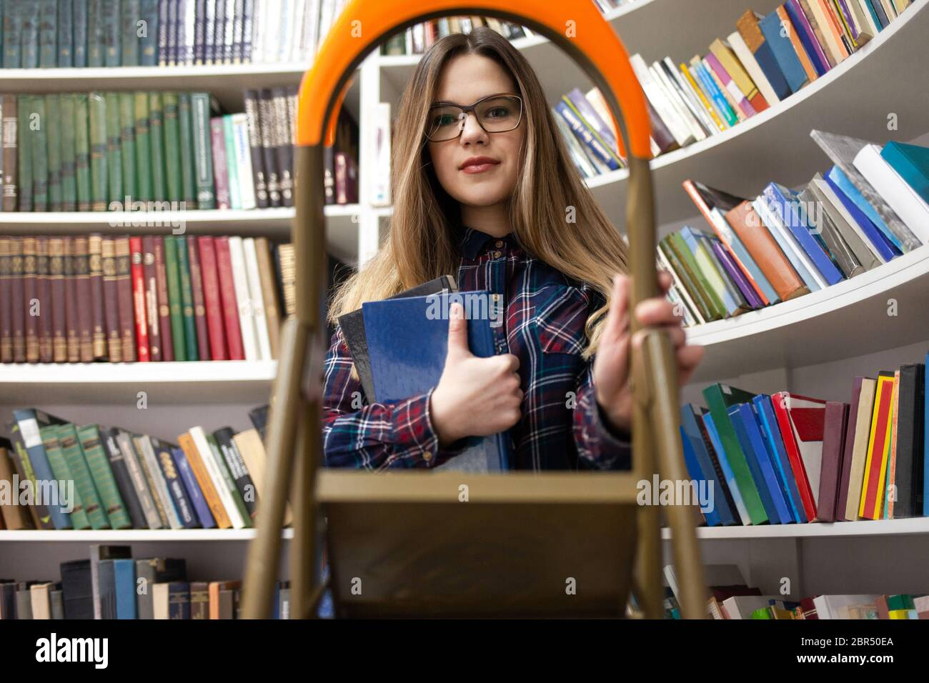 Pretty student lady stands on a stepladder in a library holding a book in her hand. Woman in public library Stock Photo