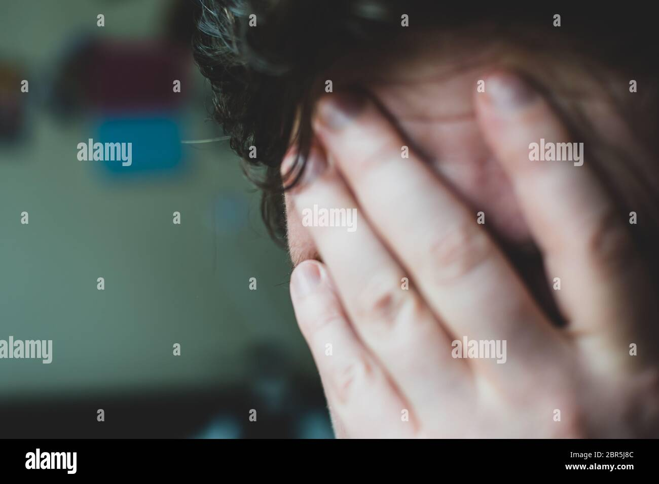An overwhelmed man covers his face with his hand. Stock Photo