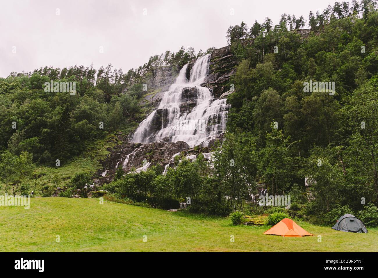 Tvinde Camping tents on the background of a waterfall Tvindefossen in Norway near Voss. Campsite in the norwegian fjords Stock Photo
