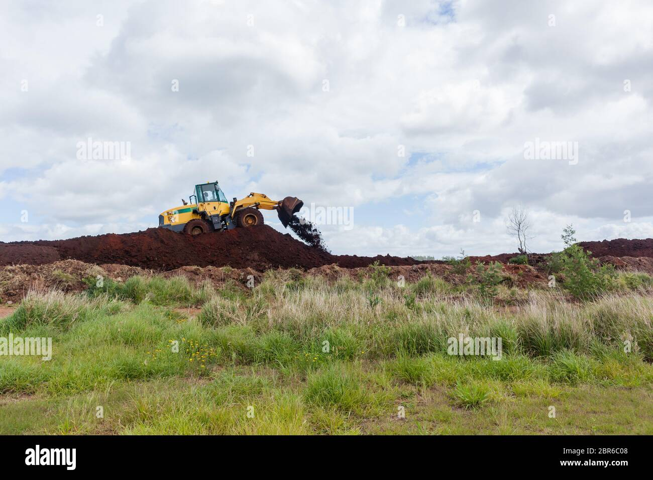 Industrial earthworks  loader bucket machine on building construction site. Stock Photo