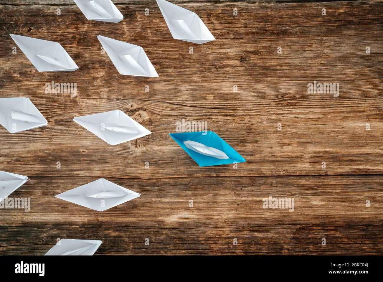paper boats on aline on the wooden background, concept teamwork, leadership and management Stock Photo