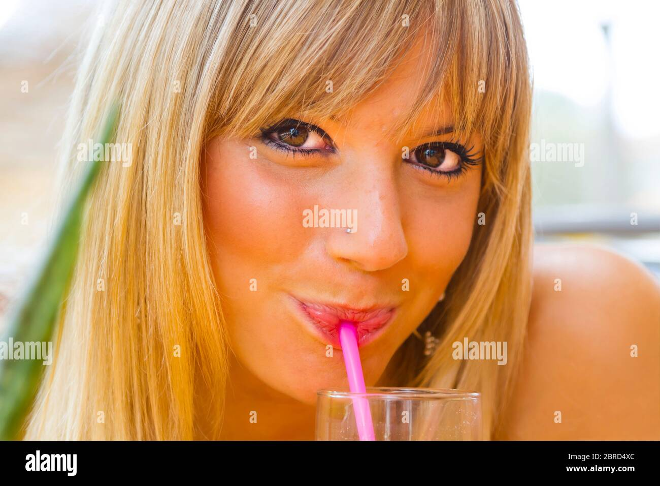 Cute blonde teengirl headshot eyeshot drinking sucking suck juice though using use plastic Pink straw in bar beachbar slight smile Stock Photo