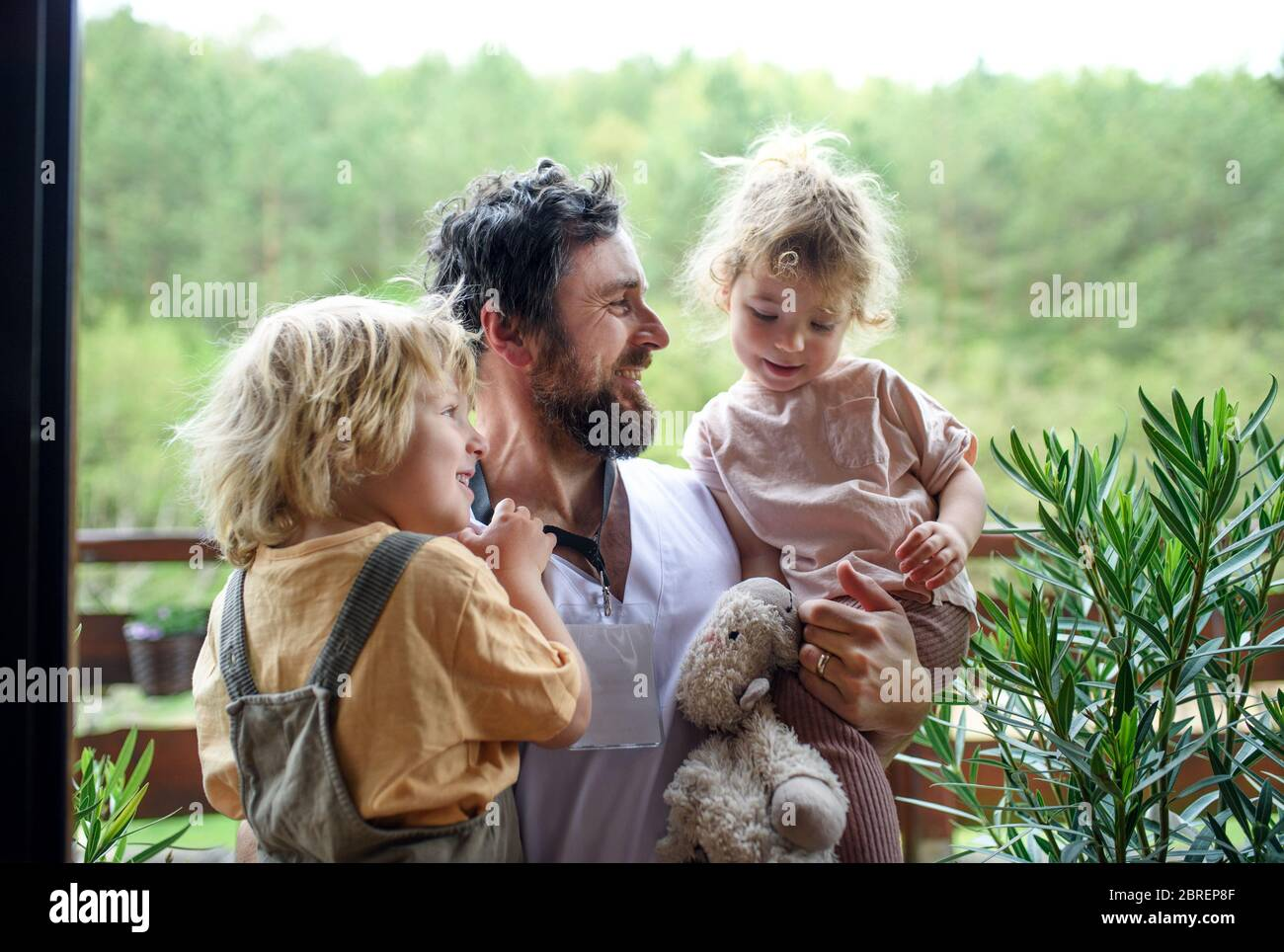 Father doctor finally at home meeting his children, end of coronavirus. Stock Photo