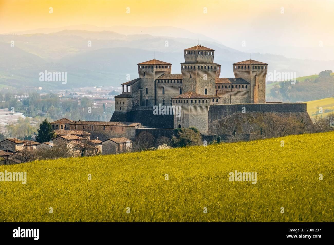 landmarks of italy, the Torrechiara fantasy castle near Parma - Italy with yellow warm toned grass and sky vintage look with copy space Stock Photo