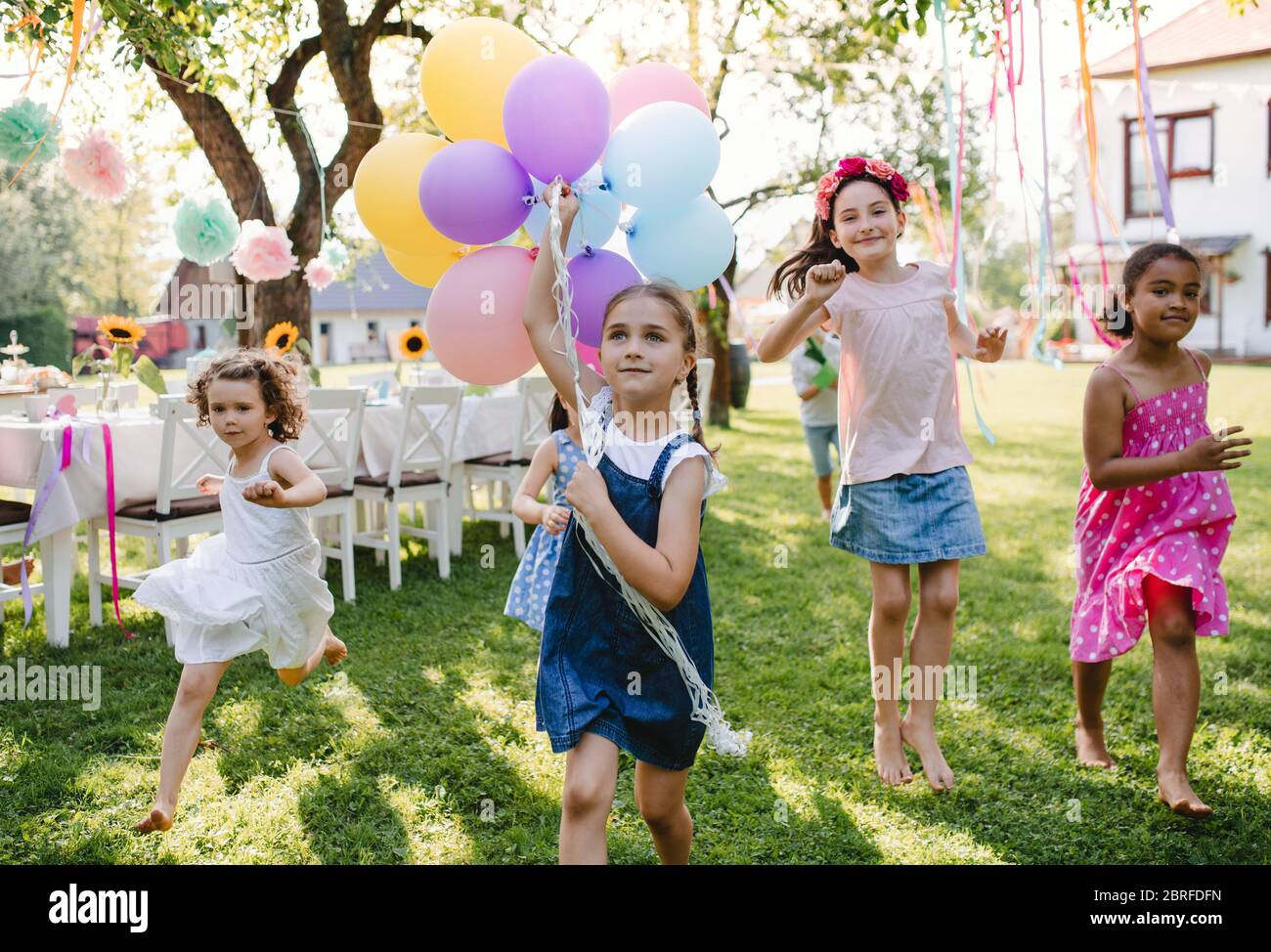 Small children outdoors in garden in summer, playing with balloons. Stock Photo
