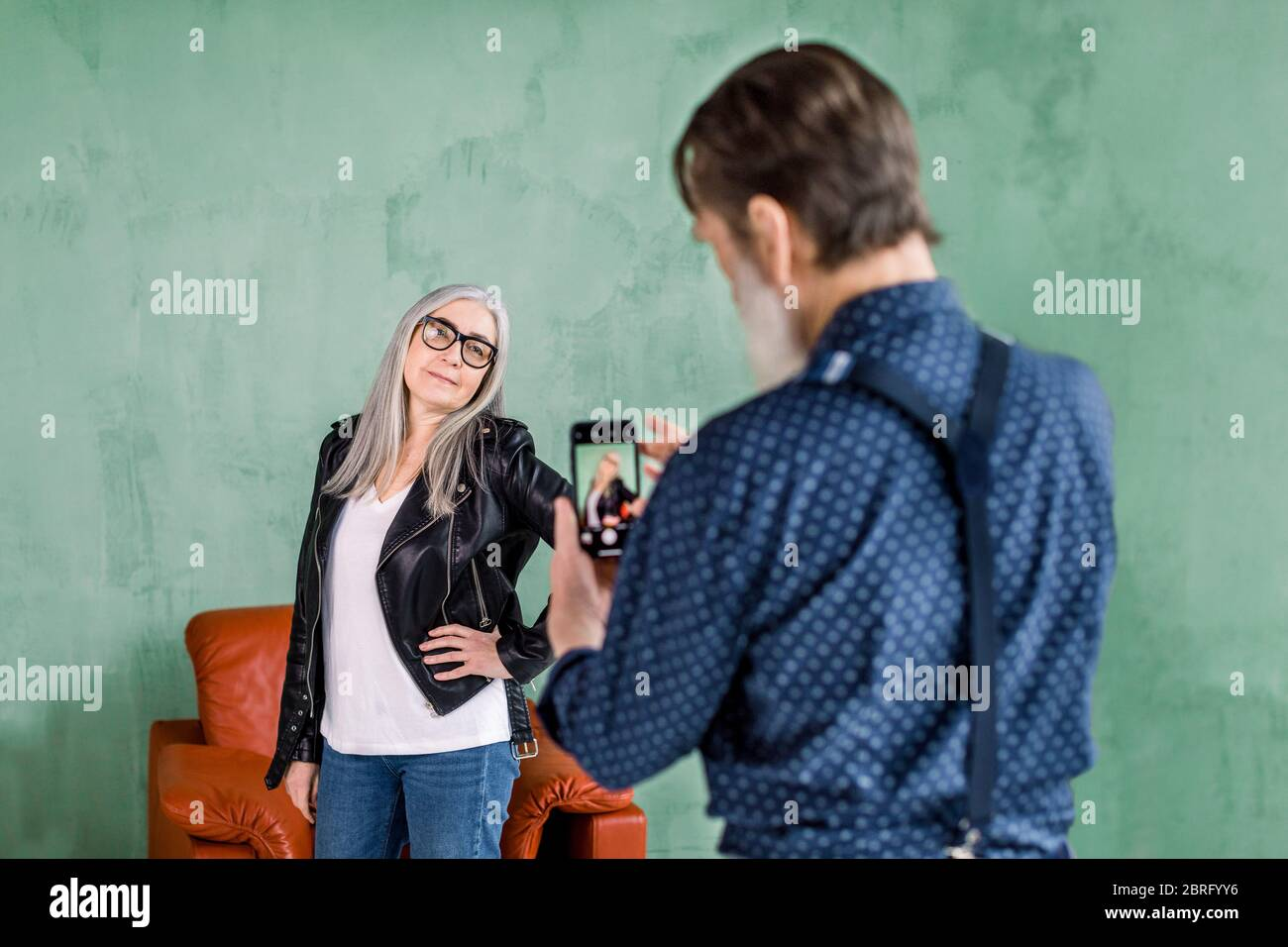 Portrait of handsome elderly man taking picture of his lovely cute beautiful gray haired woman posing to camera and smiling. Senior couple having fun Stock Photo
