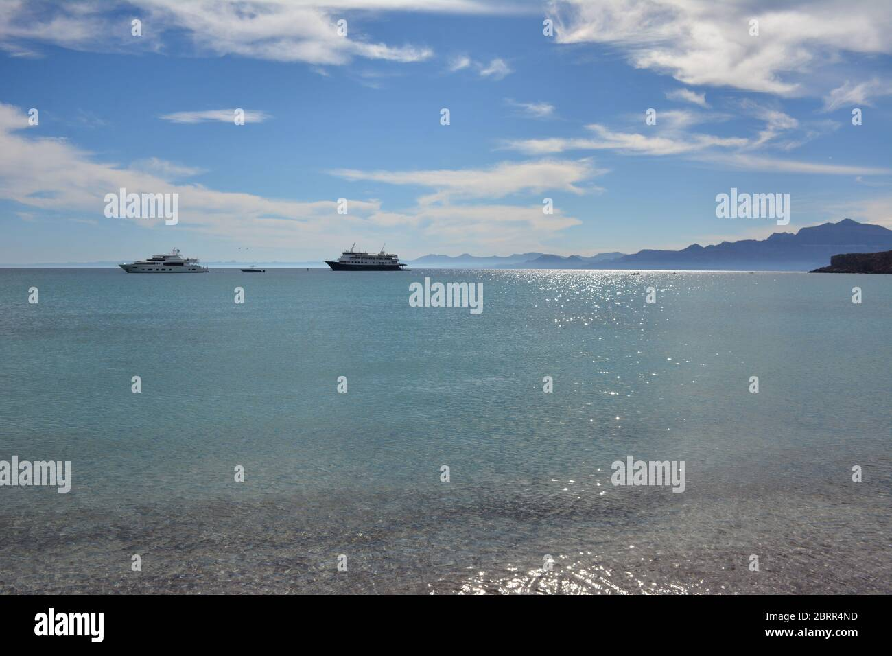 Clear glittering sea with a cruise ship and yacht in the background at Isla San Francisco, Sea of Cortez, Baja California Sur, Mexico. Stock Photo