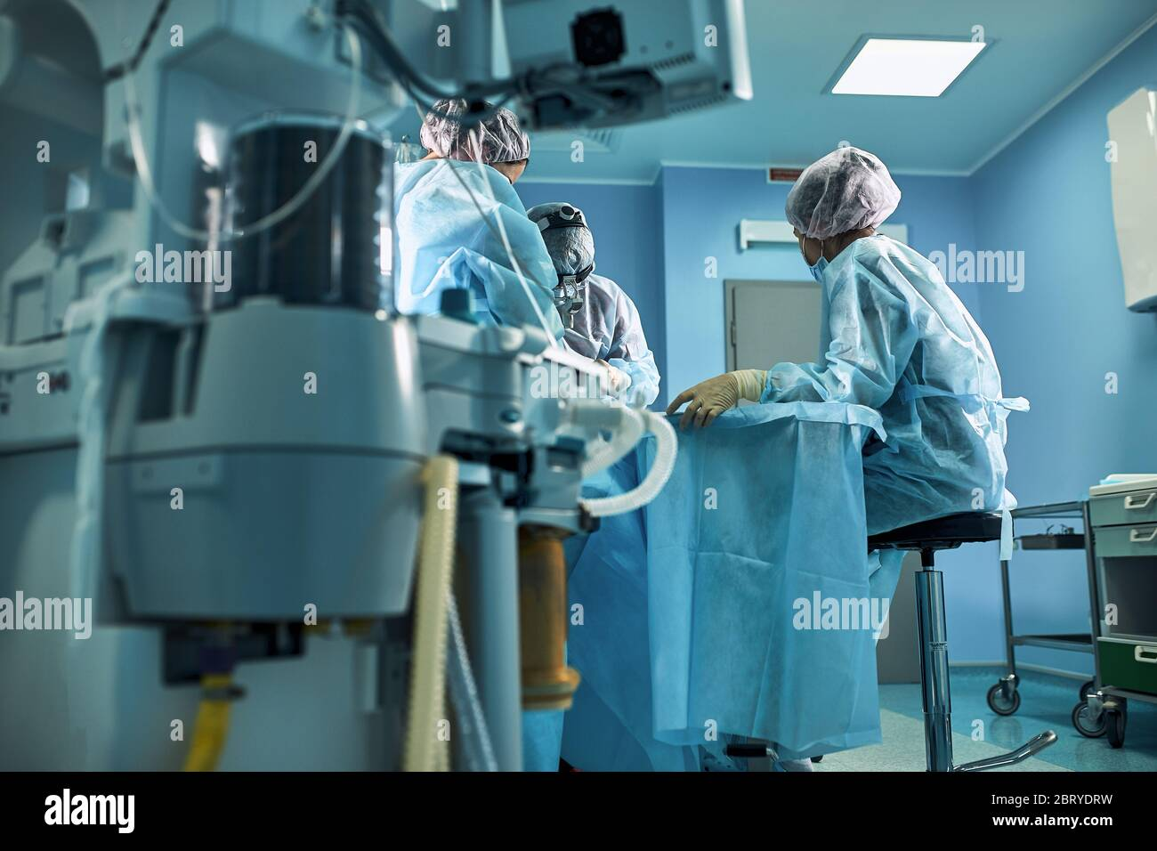 Hospital, surgical operating room. Life saving. Ventilation of the lungs with oxygen. Against the background of a team of surgeons during the Stock Photo