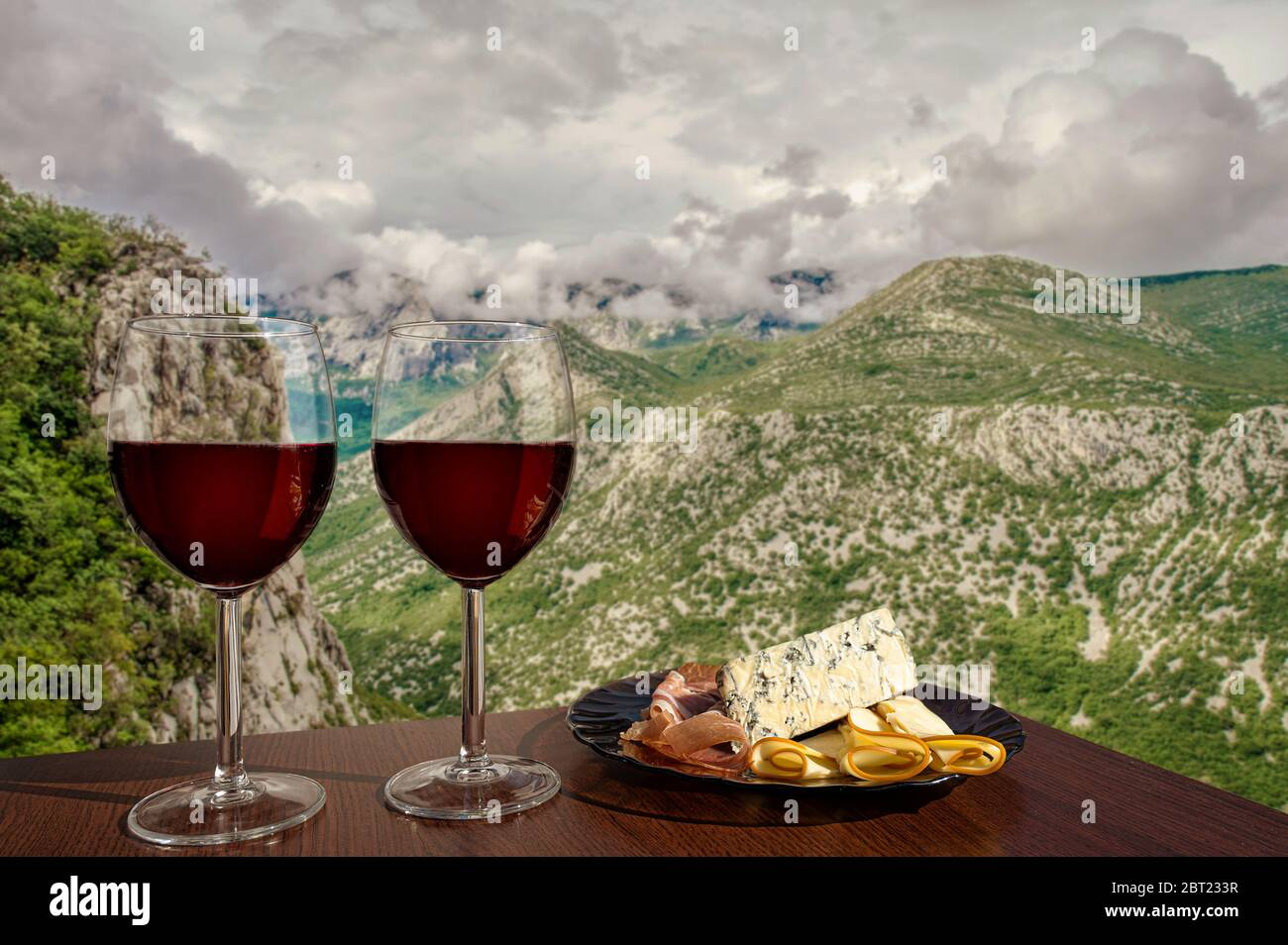 Two glasses of wine with charcuterie assortment on view of mountains with clouds in Croatia. Dinner in cafe or restaurant with mountains view. Stock Photo