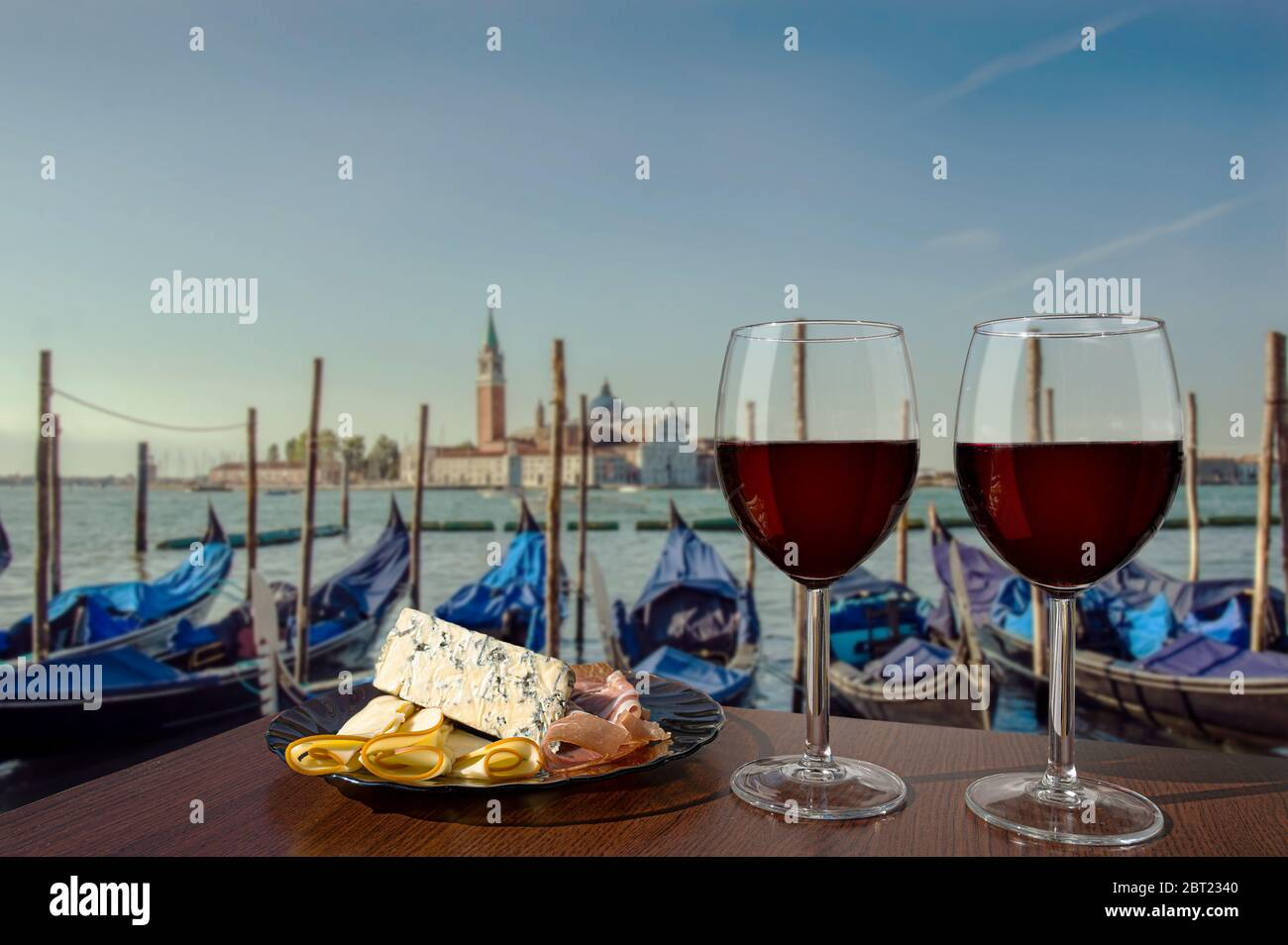 Two glasses of wine with charcuterie assortment on view of gondolas and San Giorgio Maggiore church in the background in Venice. Glass of red wine wit Stock Photo