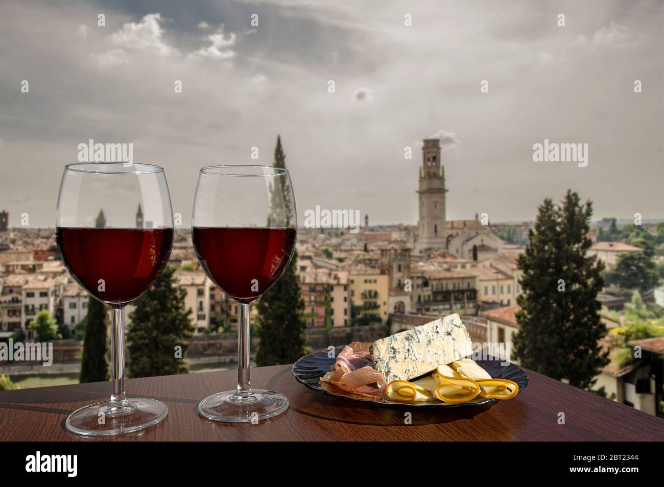 Two glasses of wine with charcuterie assortment on view of Verona, Italy. Glass of red wine with different snacks - plate with ham, sliced, cheese Stock Photo