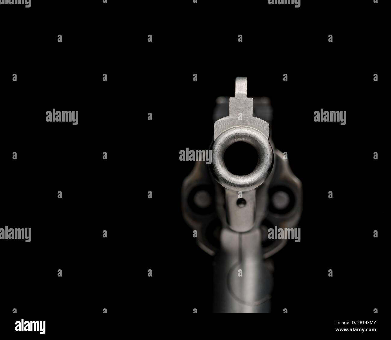 Looking down barrel of gun, pointed toward you, isolated on black background. Concept of crime, violence, shooting, firearm control and safety Stock Photo