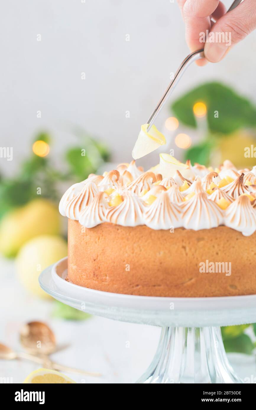 Woman decorating a Lemon curd and Meringue Cake on a cakestand Stock Photo