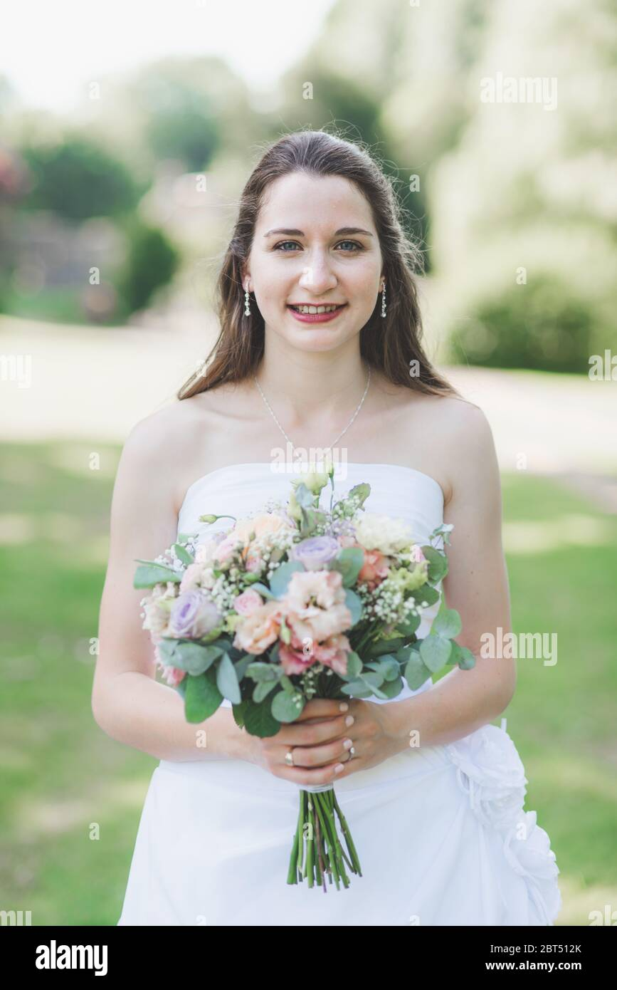 Portrait of a smiling bride holding a wedding bouquet Stock Photo