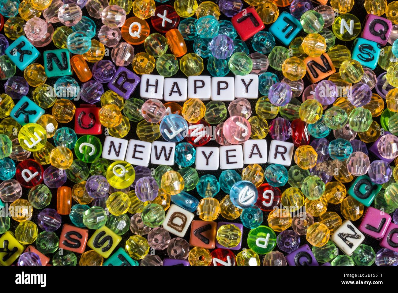 Happy New Year phrase surrounded by beads and alphabet blocks Stock Photo