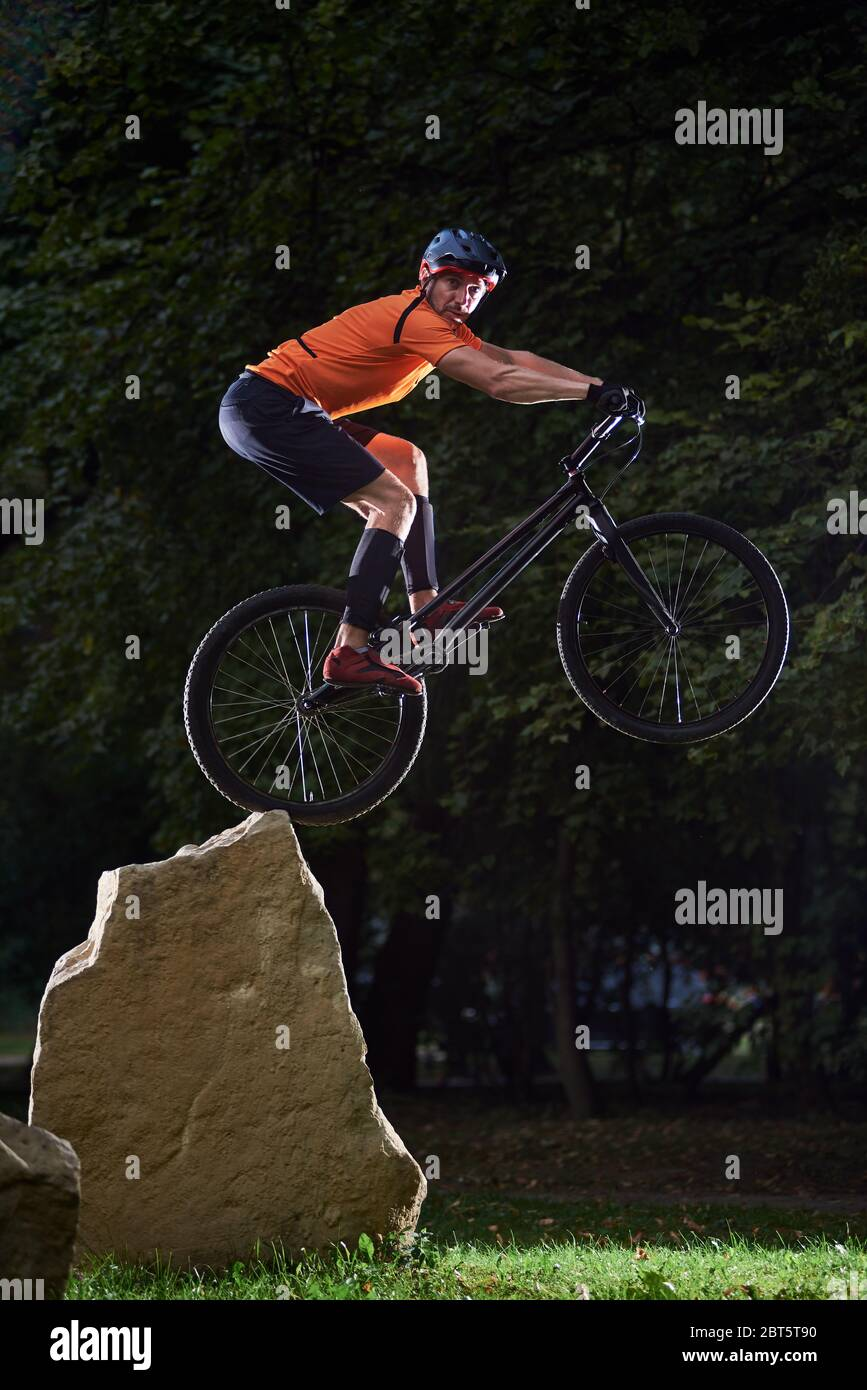 Front view of cyclist looking into camera during a high jump on a bicycle. Athlete keeping balance on back wheel of mountain sports bike. Concept of active lifestyle. Stock Photo