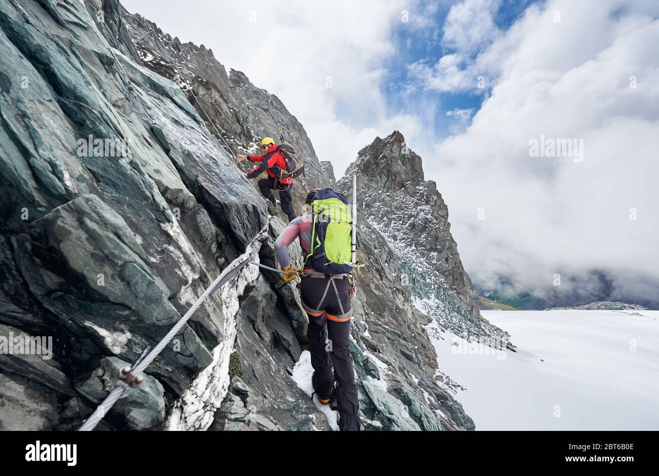 Back view of rock climbers with backpacks using fixed rope while ascending high rocky mountain. Male mountaineers climbing natural rock formation and trying to reach mountaintop. Stock Photo